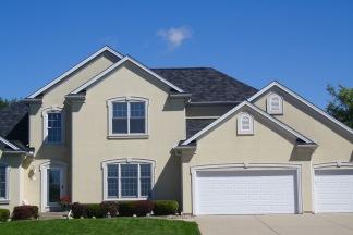 grand stucco home with fancy shingles