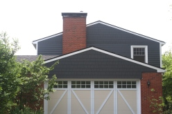 Dark grey siding, dark grey straight edged shakes, carriage style over lay garage doors, red brick