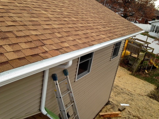 leaf protection on tan house with white gutters