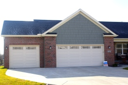 Ranch style green home with red brick, tan garage doors