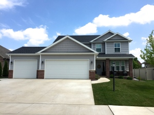 two story home with grey siding and grey shakes, black roof, eyebrows over garage, white garage doors and red brick