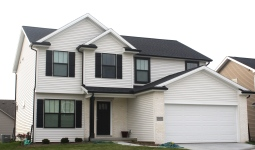 two story house with white siding, white trim, white brick, black roof, and black gutters