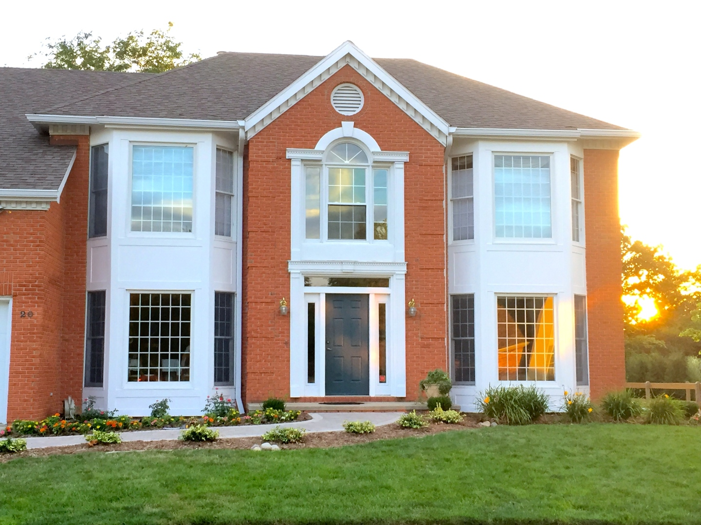 Two story bay windows in orange brick home with withe dentil moulding