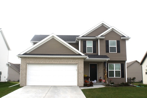 2 story house with dark brown siding, white trim, white garage door, tan brick and black roof. black raised panel shutters