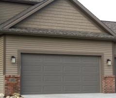 bronze garage door in tan siding and brown trim with red brick
