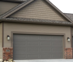 bronze garage door in tan siding and brown trim with red brick