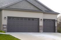 Brown garage doors in tan siding and brown brick