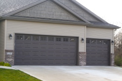 Brown garage doors in tan siding and brown brick