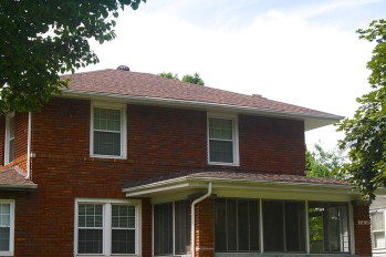 two story brick historic home with burnt sienna roof