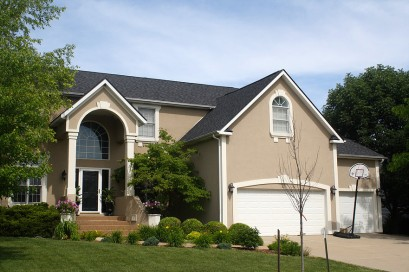 Faux Stucco style two story home, keystone accents in windows and garage doors, black roof