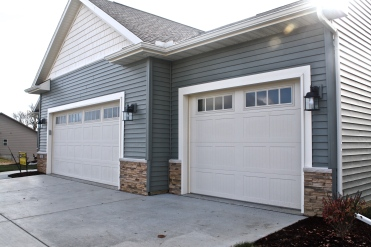 cream carriage style garage door in green home and tan stone