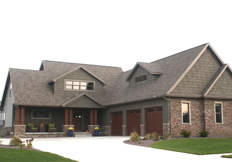 grand two story house with cedar columns, brown brick, faux wood garage doors, dark siding and dark shakes