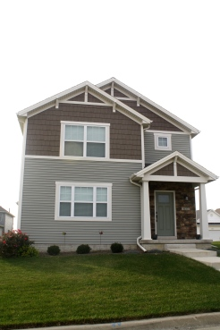 two story house with green siding and dark brown shakes cream trim, cream gable accents