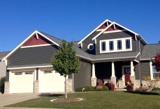 two story dark grey-green siding with cream trim, red gables and stone accents