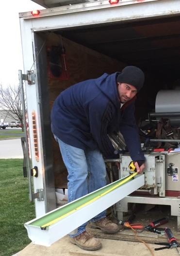 man working a seamless gutter machine