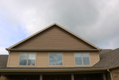 Gable shakes are hard board in chestnut brown, siding is hardboard latte tan, and weathered wood shingles