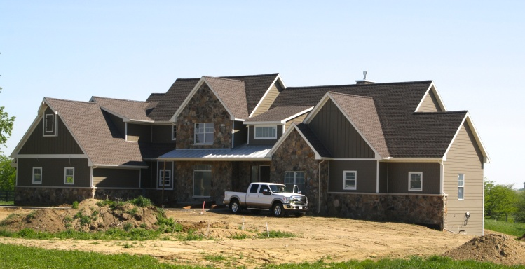 Large two story farmhouse with stone accent, bark colored fiber cement siding, metal roof accent, and white trim