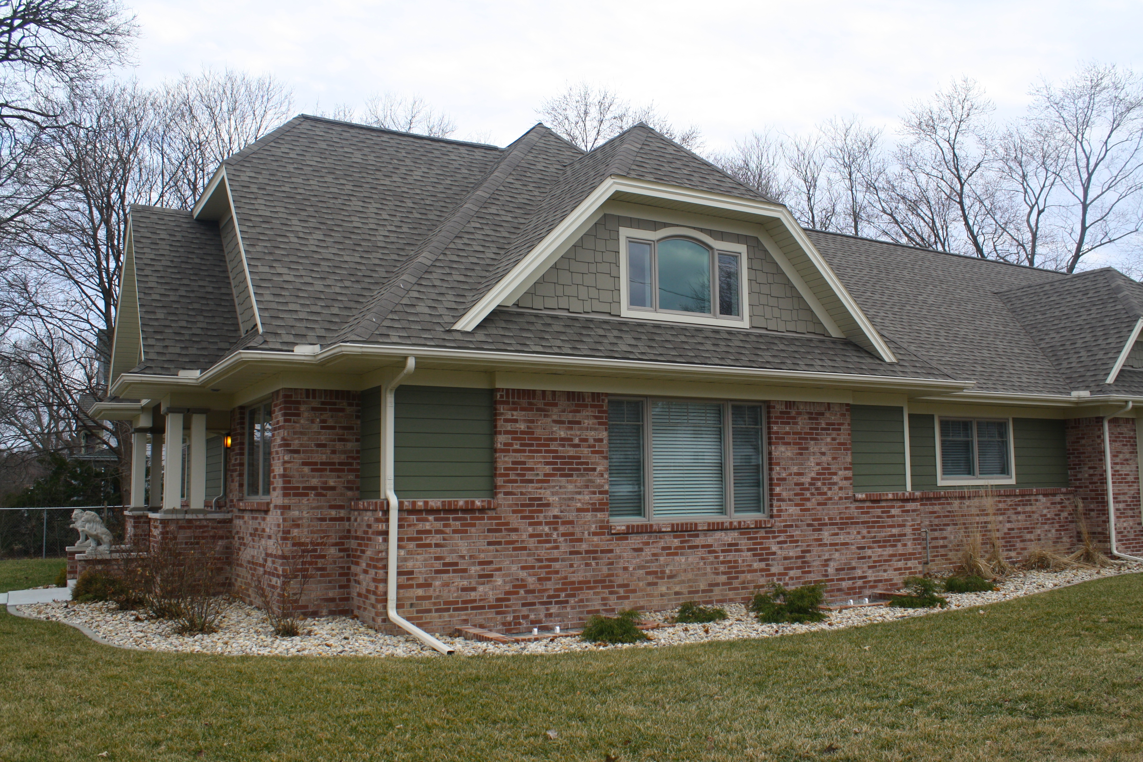 A House With Steep Roof Lots Of Red Brick And Green Siding