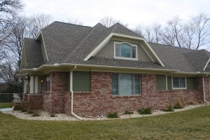 a house with a steep roof, lots of red brick, and green siding and shake