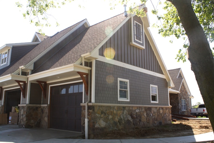 Large Farm house garage with stone, fiber cement straight edged shake in bark, board and batten fiber cement in bark, with cream accents. Wooden corbels in garage