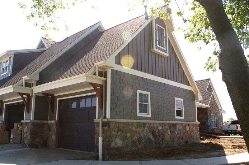 two story farmhouse garage with wooden corbels, stone accents, straight edged shake and vertical siding