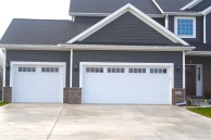 white carriage style garage doors in dark grey garage with brown brick
