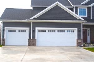 white carriage style garage doors in dark grey garage with brown brick