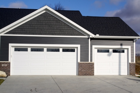 two white garage doors with plain glass inserts in red brick and grey home