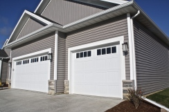 grey house with 2 white carriage style garage doors