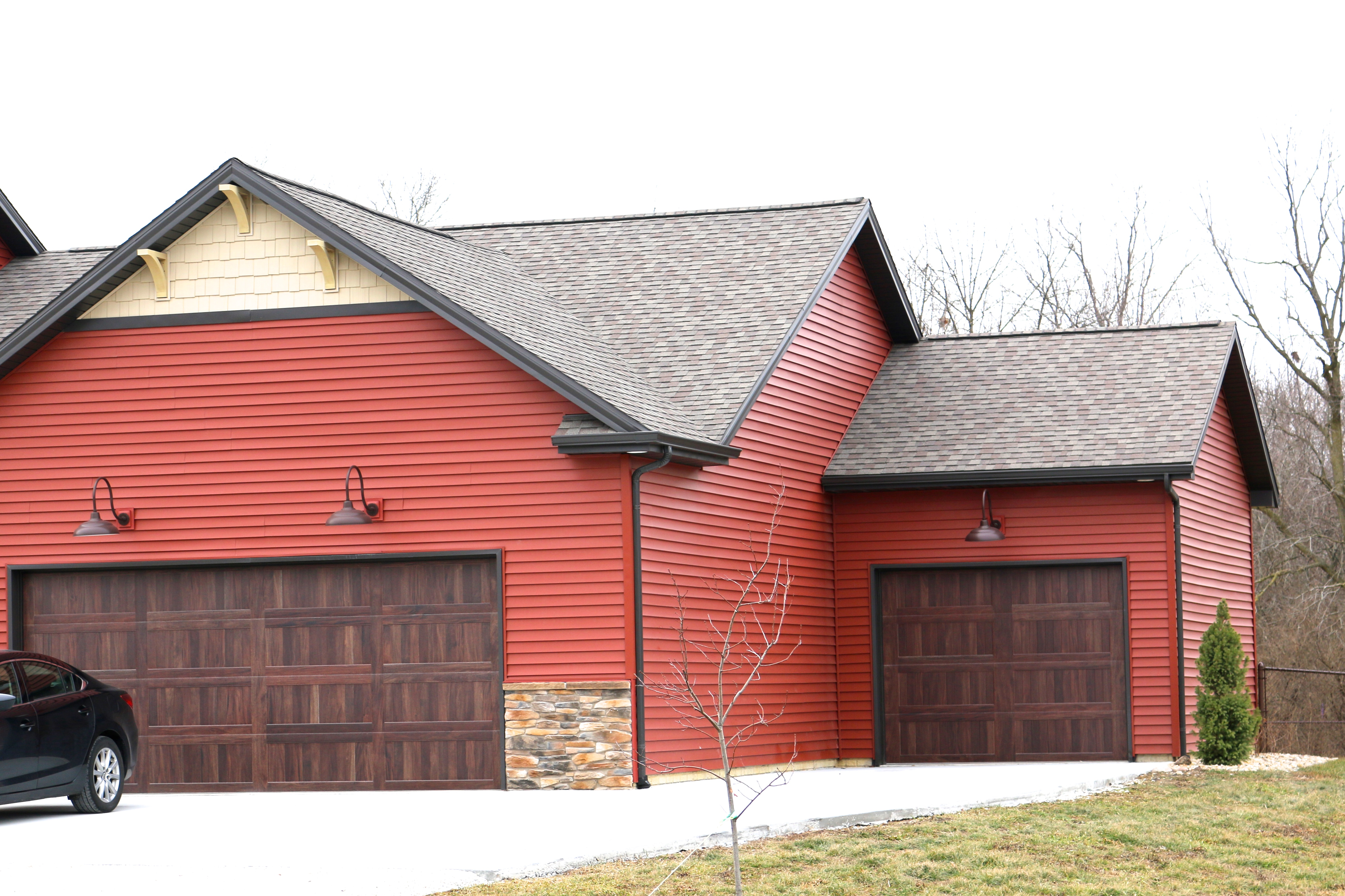 Mahoghany Garage Doors With Red Siding And Weatherered