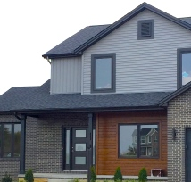 two story ranch with dark grey siding, black trim, real cedar siding, black garage door, dark brown brick