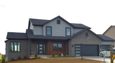 two story ranch with dark grey siding, black trim, real cedar siding, black garage door, dark brown brick