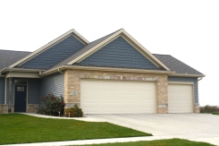 garage with cream garage doors, light blue siding, dark blue shakes, tan brick with stone accents
