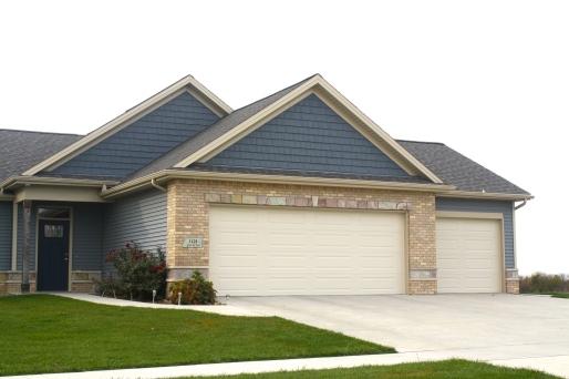 garage with cream garage doors, light blue siding, dark blue shakes, tan brick with stone accents