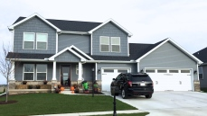 two story blue house with black roof and white trim. White carriage style garage door