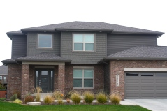 2 story house with dark siding, brown trim, dark brown garage door and red brick