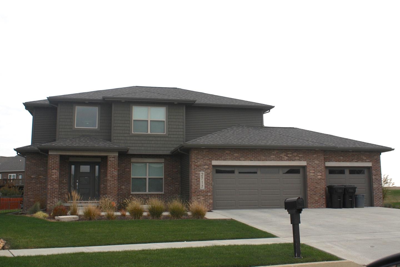 2 story house with dark siding, brown trim, dark brown garage door and red brick