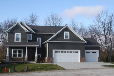 two story house with dark siding, craftsman style columns, white garage doors