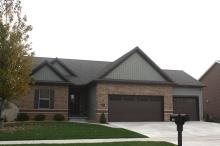 Green ranch with brown brick brown garage doors, brown roof