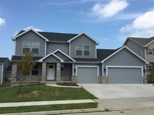 grey sided house with grey shakes and light grey trim with black roof, grey garage door no windows in garage doors, tan bricks