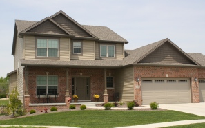 2 story house with tan siding, dark brown shakes, red brick, tan garage door