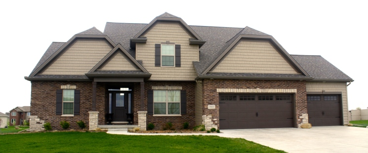 2 story house with tan shakes, dark brown brick, brown roof and brown carriage style garage door