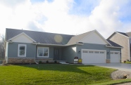 ranch style green home with came shakes and cameo trim and cameo garage doors