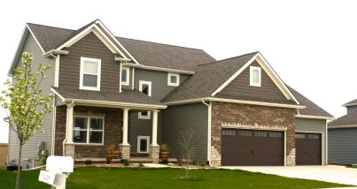 two story ranch with green siding, brown cedar shakes, cream trim, brown brick with stone accents