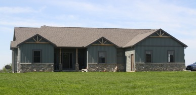 Green ranch style home with real cedar starburst gable accents and stone half way up the wall