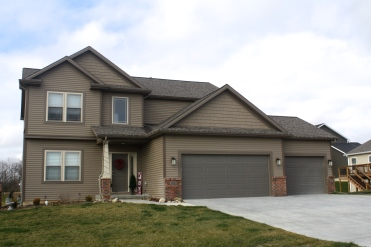 two story brown house with dark brown tim and brand garage door