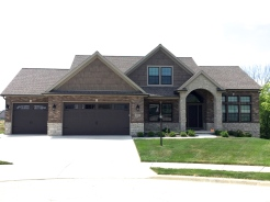 big house with tan siding and brown shakes, brown brick and stone front with brown carriage style garage doors