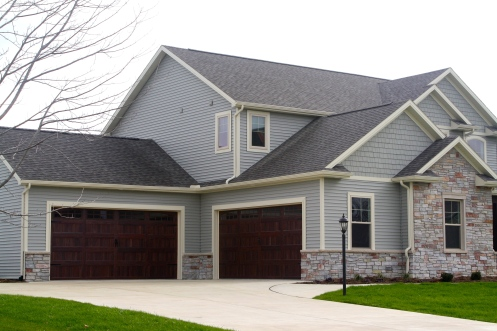 wooden garage doors in green home with cream trim and stone accents