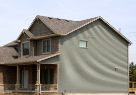 two story house, green siding, cedar shakes with decorative gable accent