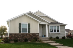Small one story home with green and white siding